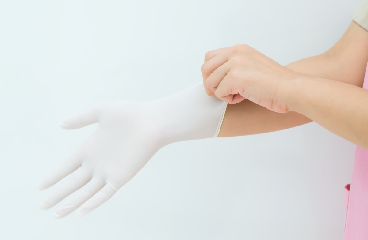 Doctor or nurse putting on protective gloves, on light background,woman surgeon doctor wear glove before operation.