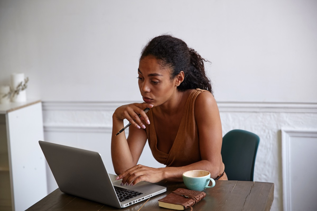 Beautiful dark skinned businesswoman with casual hairstyle working on her laptop, looking at screen with concentrated face and touching chin with hand