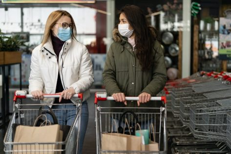 Two women in a medical mask enter a modern grocery market, a store. Coronavirus protection, quarantine, self-isolation.