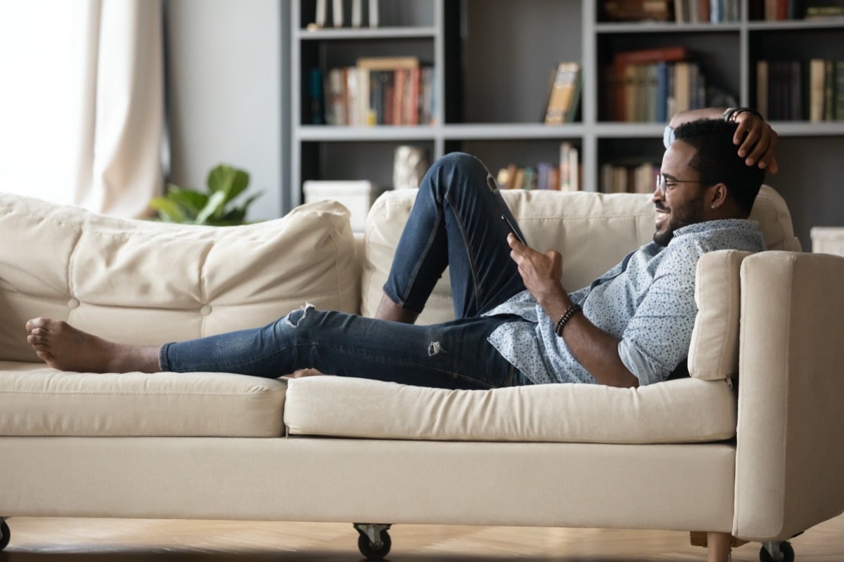 Young black man reclining on couch and reading tablet