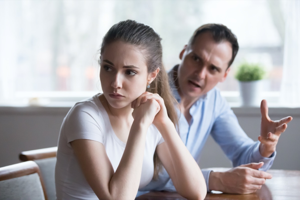 Offended woman sitting back to lover looking away avoiding talking