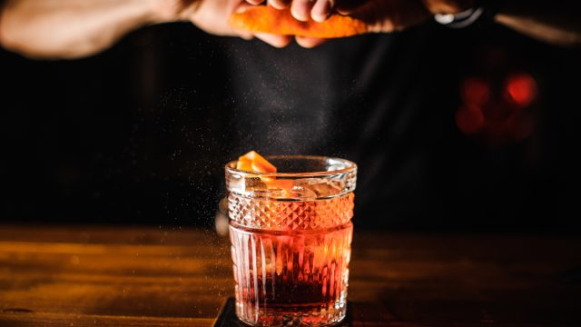 Bartender squeezing orange peel cocktail