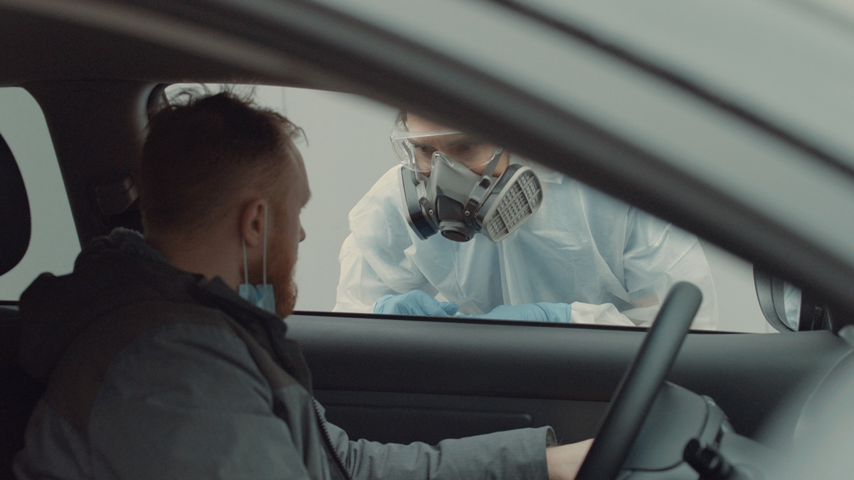 Patient is being tested in his vehicle on a drive-through coronavirus COVID-19 testing location