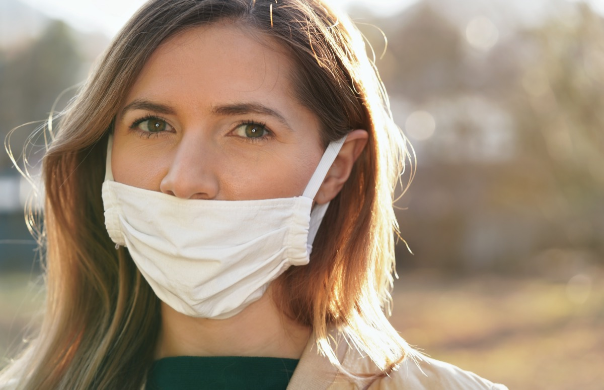 woman wears home made white cotton virus mouth face mask, wrong way, incorrect wearing