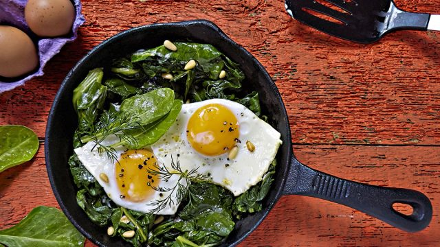fried eggs with spinach in cast iron pan