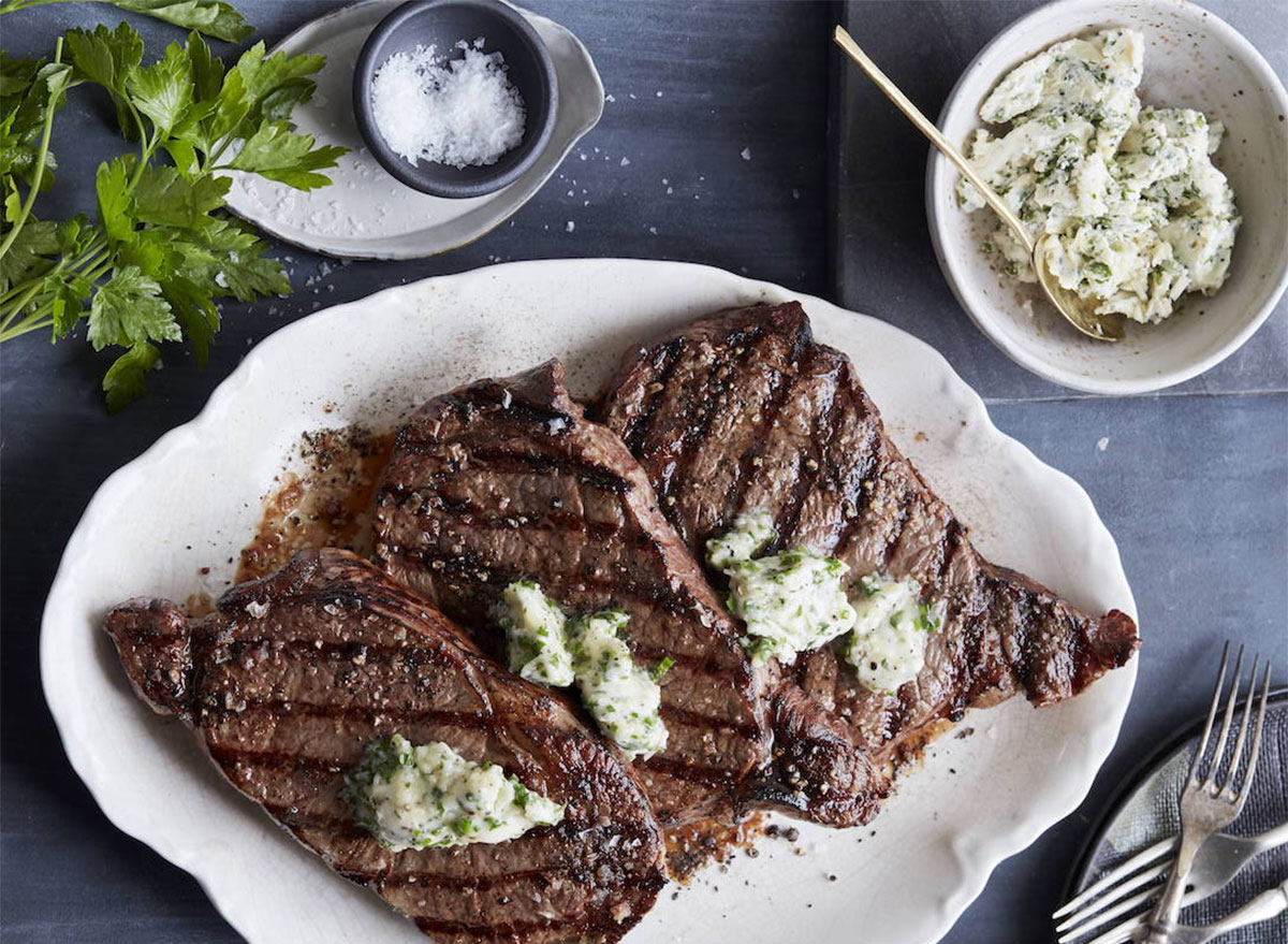 grilled ribeye steaks topped with butter