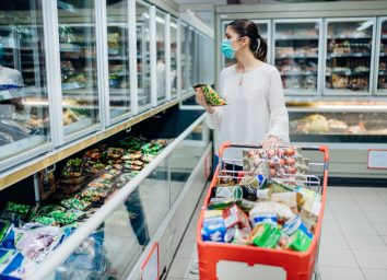 woman shopping in surgical mask at grocery store