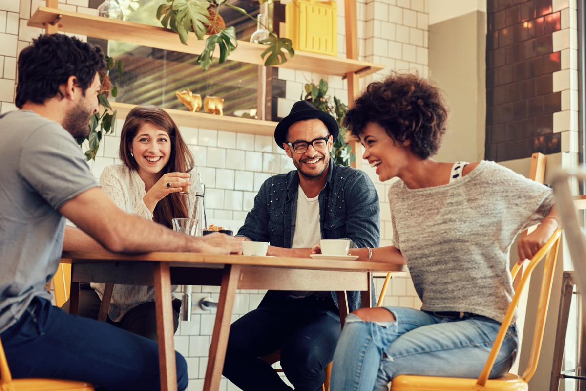 Portrait of cheerful young friends having fun while talking in a cafe