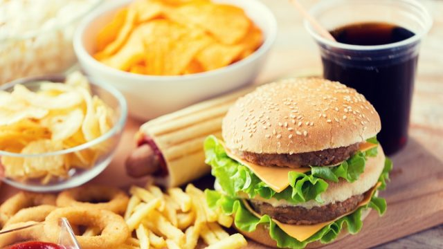 hamburger or cheeseburger, deep-fried squid rings, french fries, drink and ketchup on wooden table