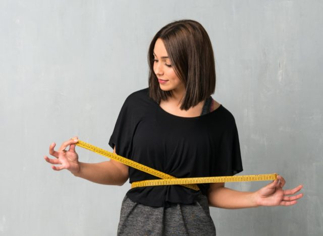 Young sport woman with tape measure