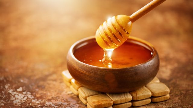 Honey dripping from honey dipper in wooden bowl