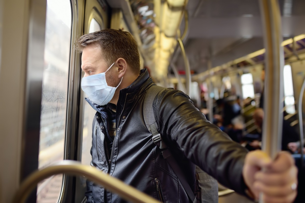Mature man wearing disposable medical face mask in car of the subway in New York during coronavirus outbreak