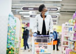 African woman wearing disposable medical mask and gloves shopping in supermarket during coronavirus pandemia outbreak