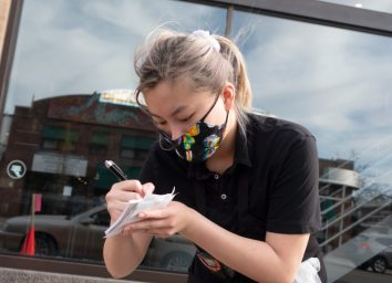 Server at the restaurant writing name and order for curbside service with mask in keeping social distance for coronavirus covid-19