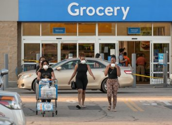 A group of African American ladies wearing protective face masks exit a Wal-Mart amid the COVID-19 epidemic