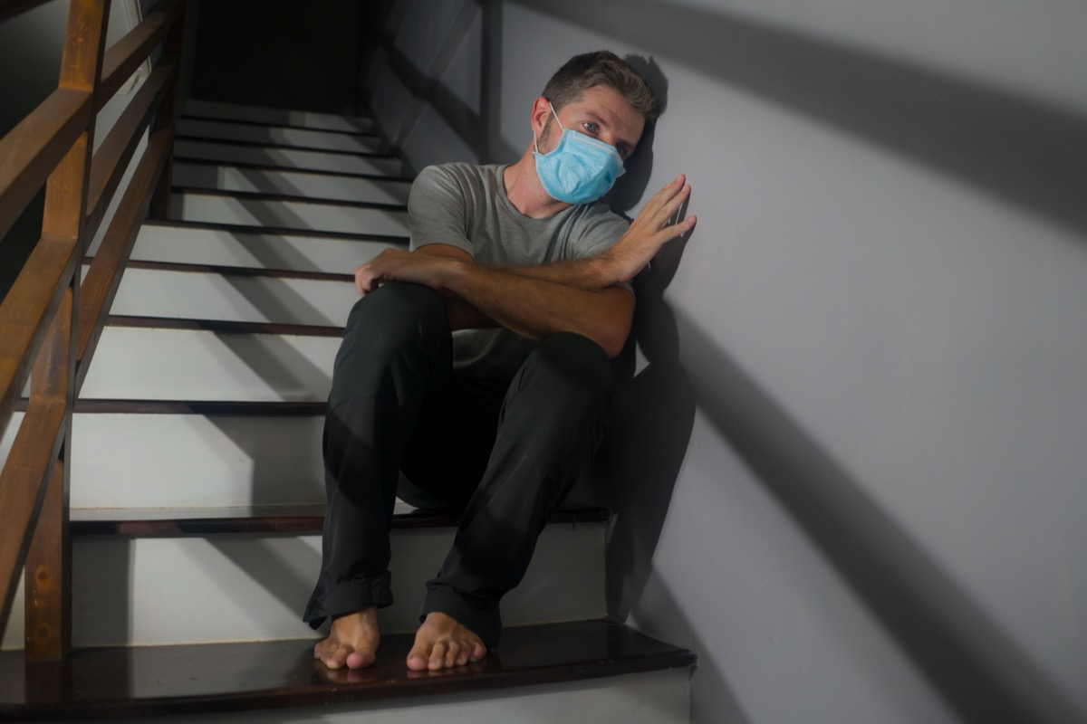 worried man in protective mask sitting on stairs at home staircase during lockdown and quarantine for covid-19