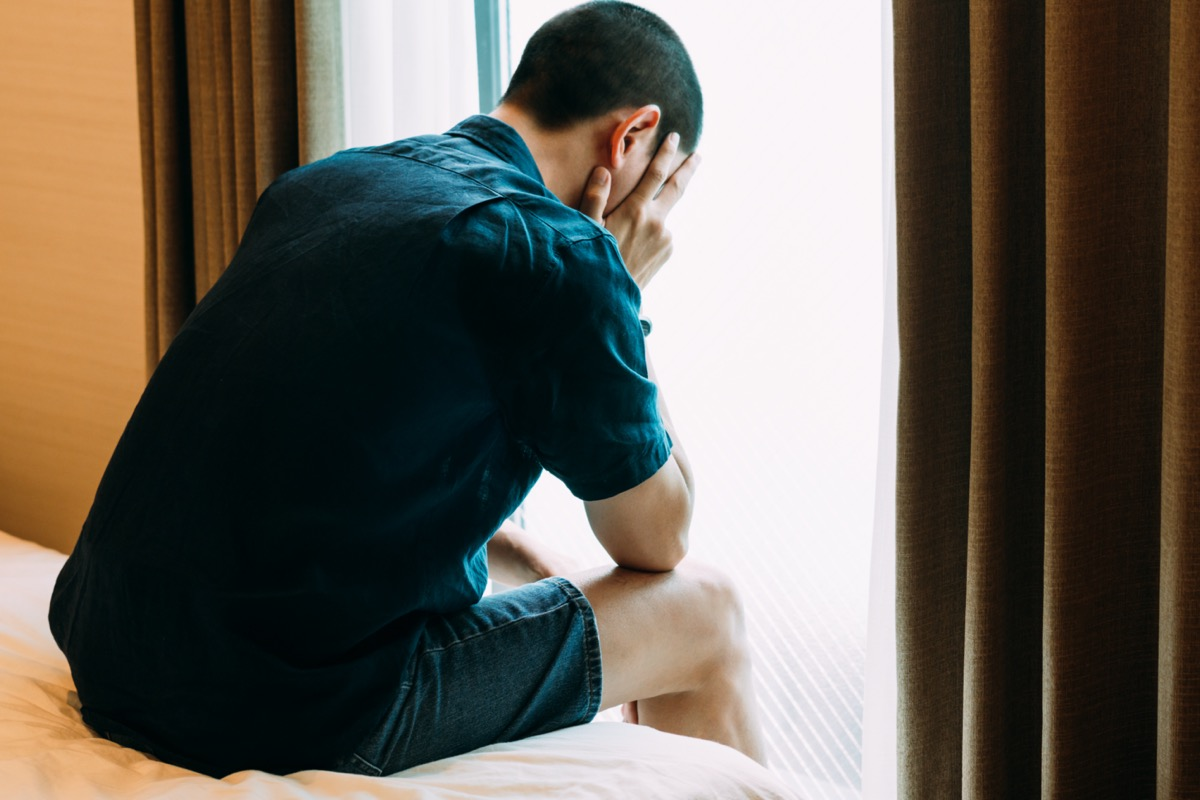 Depressed Man with Problems sitting alone head in hands on the bed and Crying