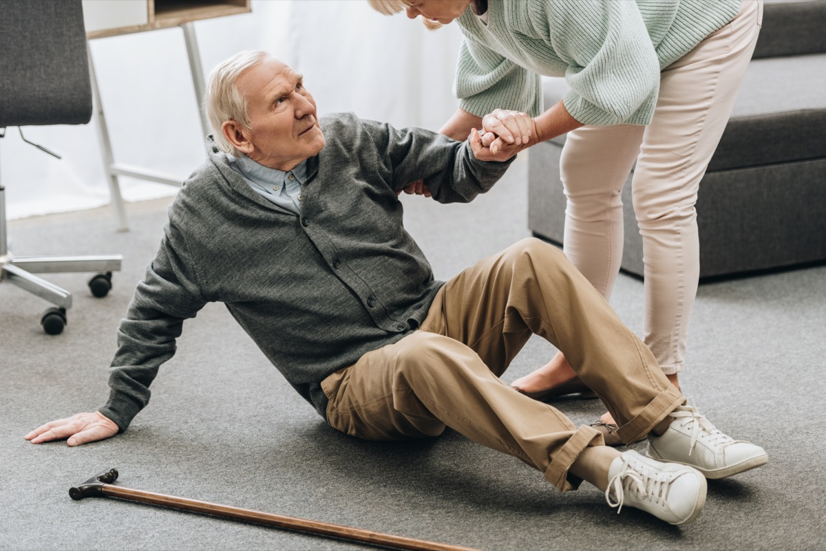 woman helping to stand up husband who falled down on floor near walking stick