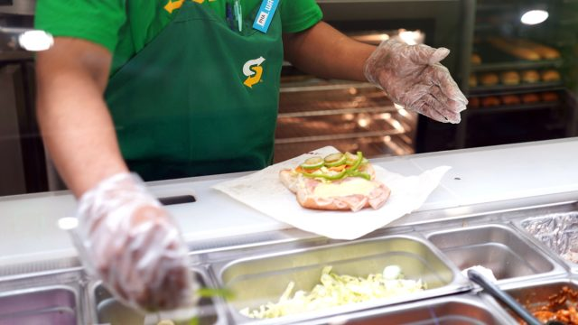 Subway sandwich artist making sub