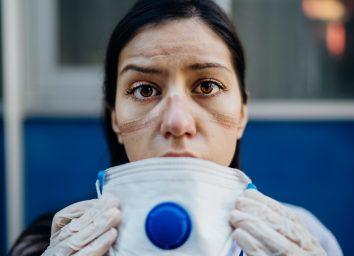Exhausted doctor / nurse taking of coronavirus protective gear N95 mask uniform