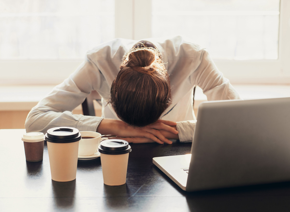 Tired woman working at her desk drinking too much coffee