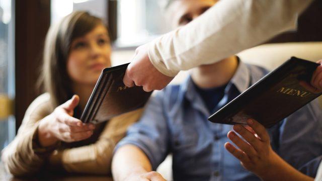 Waiter handing menu to customers