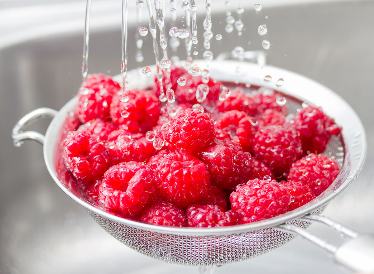 washing raspberries with water in strainer