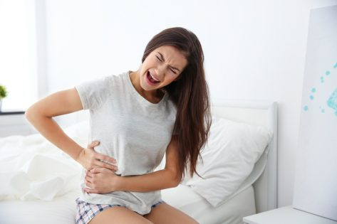 Young woman suffering pain at bedroom