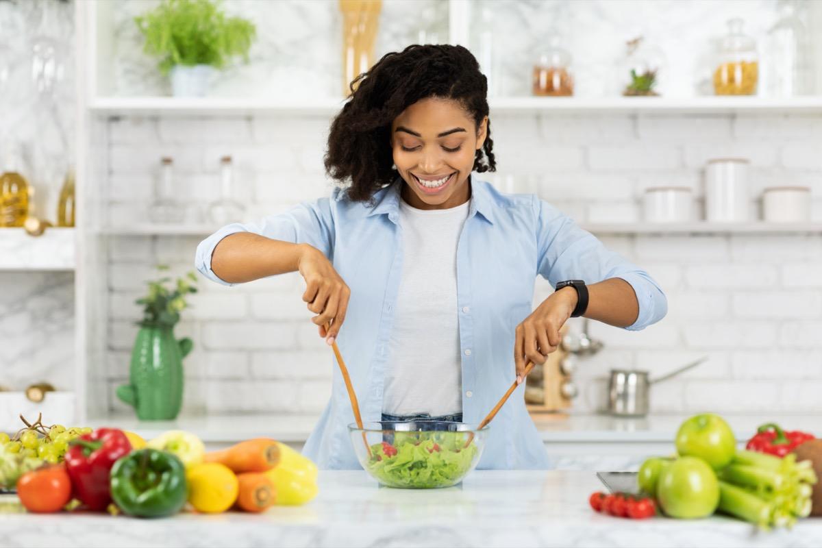 woman preparing vegetable salad in modern kitchen