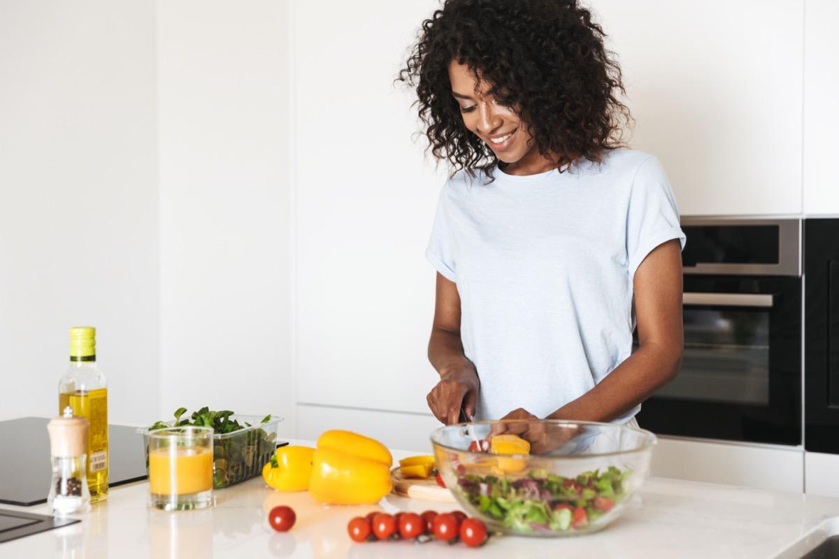 black woman cooking salad