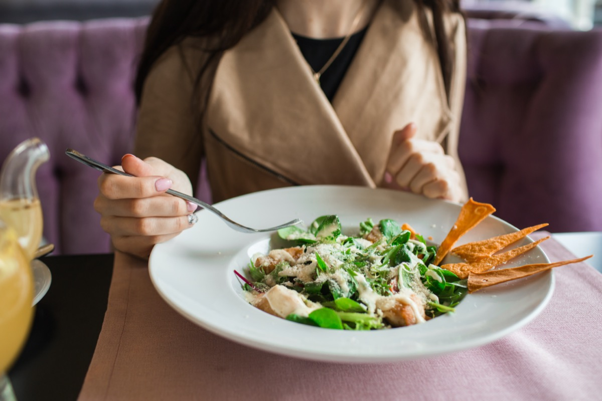 The girl in the cafe, eats Caesar salad