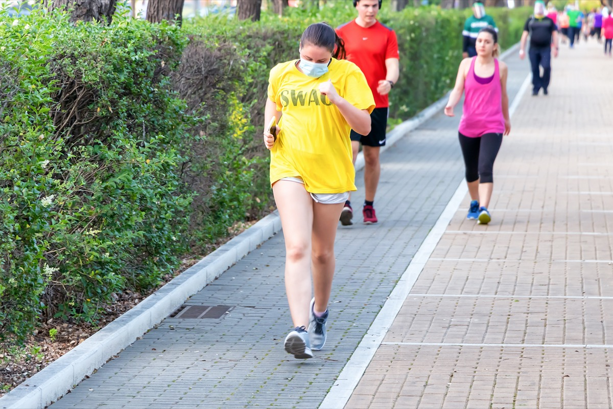 Woman running and do exercise wearing a protective face mask