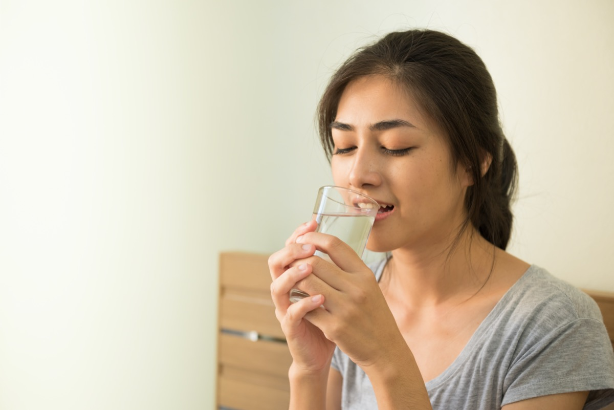 woman enjoy drinking water in the morning after wake up on the bed