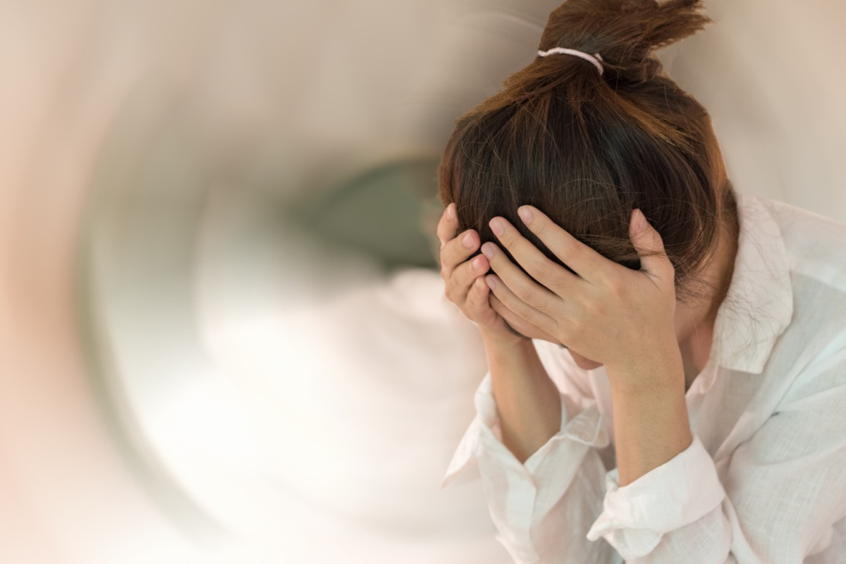 Woman hands on his head felling headache dizzy sense of spinning dizziness with motion