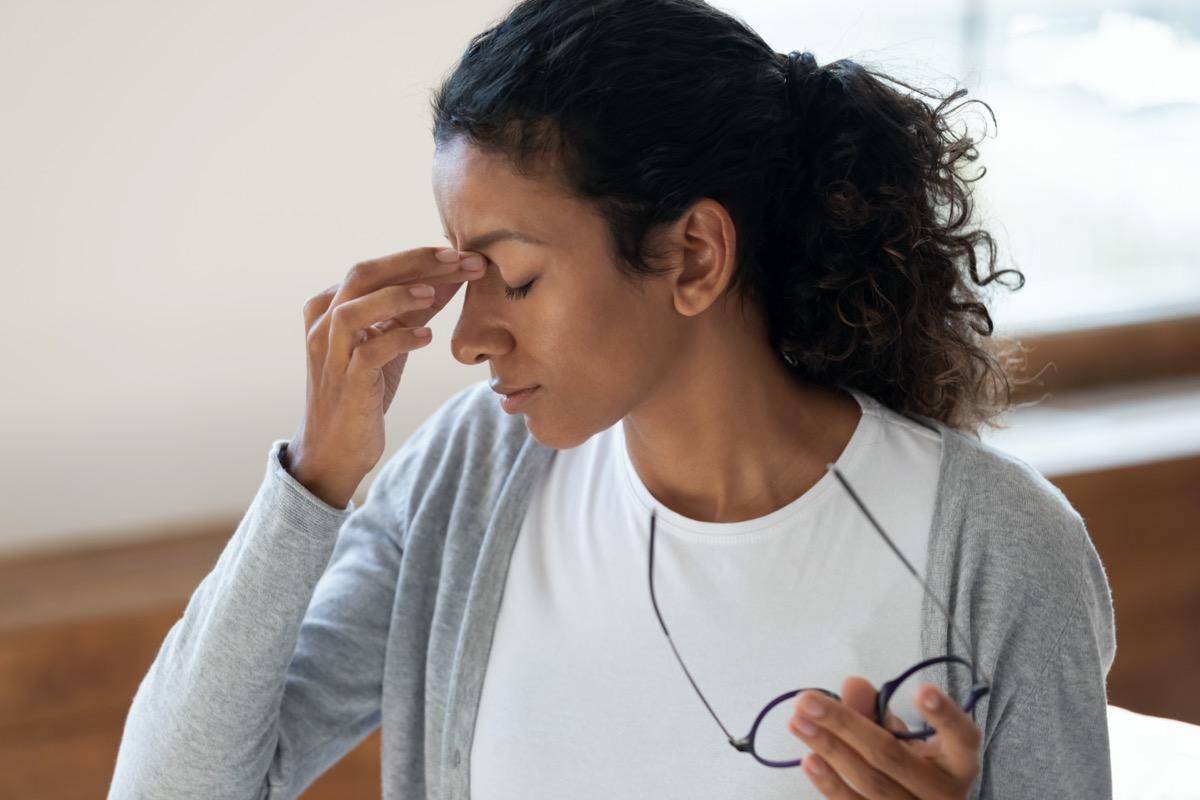 take off discomfort glasses after long wear and massages nose bridge