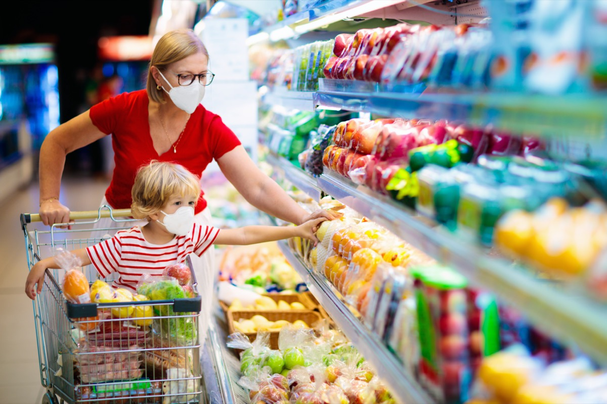 Mom and little boy buy fresh vegetable in grocery store. Family in shop.