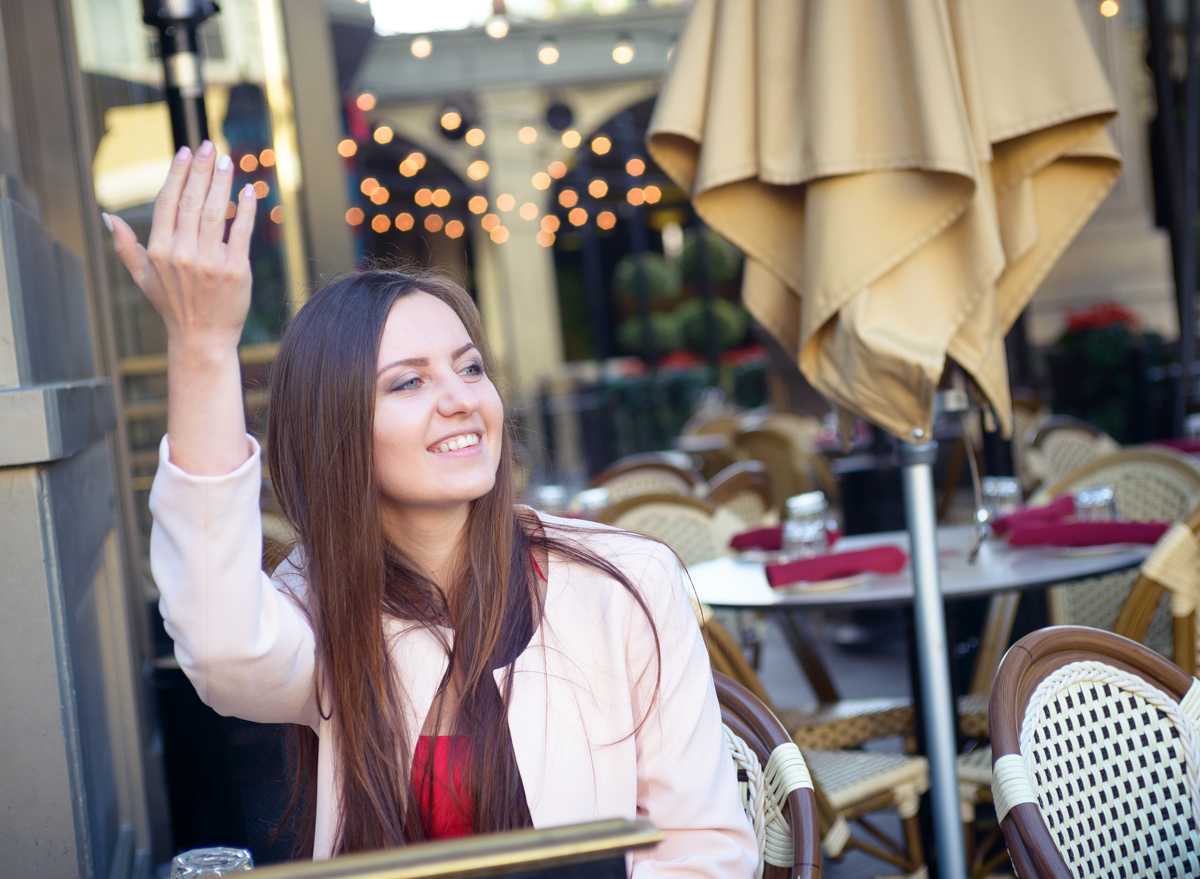 Woman motioning friends to sit down at a restaurant