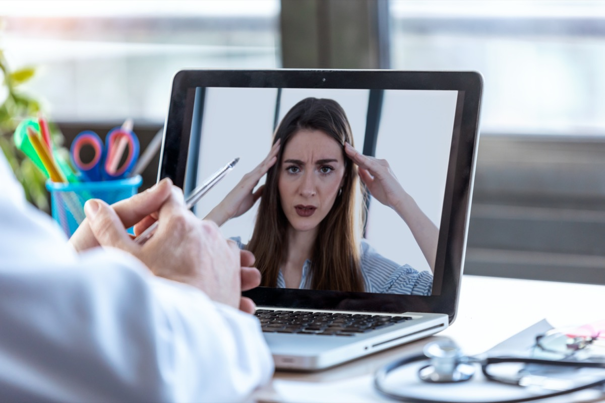 Back view of a doctor attending to a woman patient through a video call with the laptop at home.