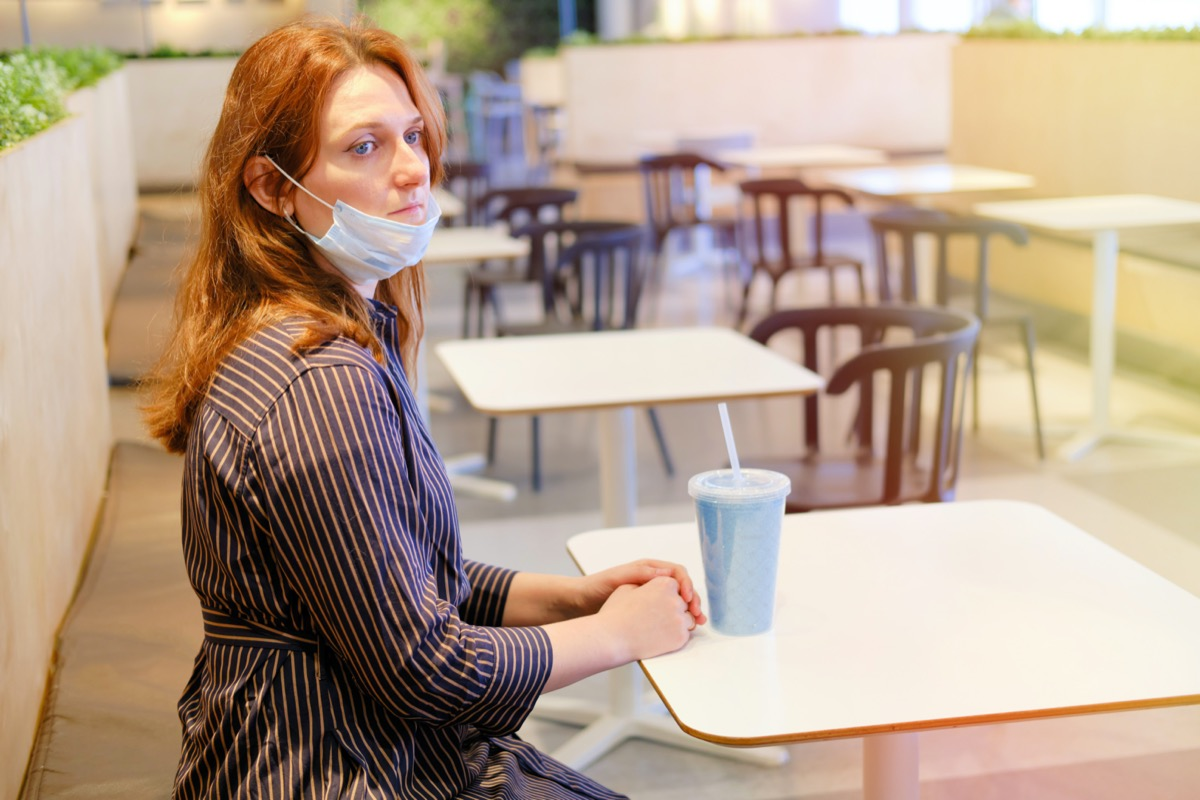 Young redhead woman with a medical mask removed sits in an empty cafe after quarantine. Deserted restaurant after the completion of the coronavirus epidemic