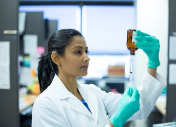 woman scientist in white labcoat holding syringe needle and brown bottle