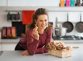 housewife with basket with mushrooms in kitchen