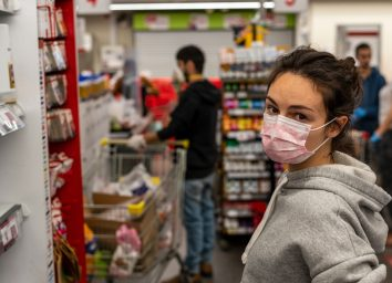 girl in a protective medical mask looks at the camera and stands in line at the cash register in a supermarket