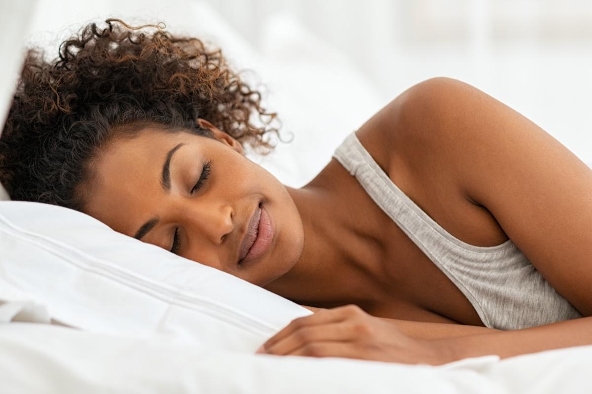 woman sleeping on bed in bedroom