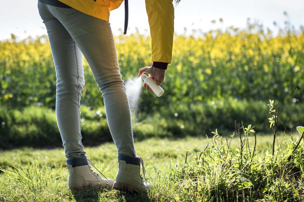 Tourist spraying insect repellent on her legs and boots