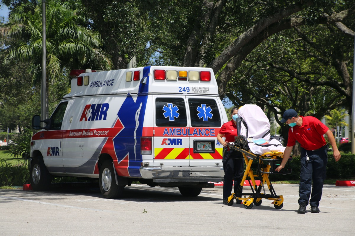 Male and female EMTs wearing face masks during Coronavirus pandemic remove gurney from ambulance parked at Boca Raton Community Hospital