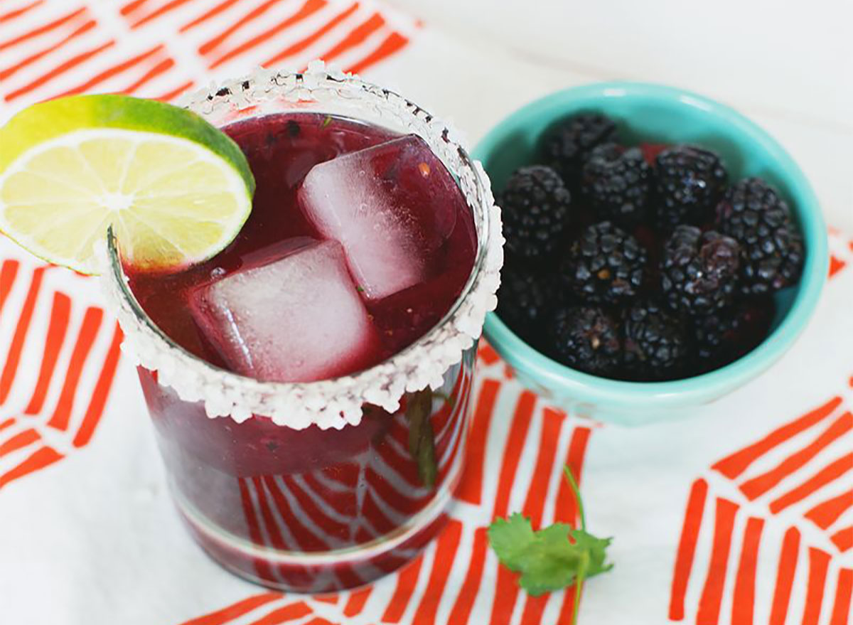 blackberry cilantro margarita in cup with blackberries on side