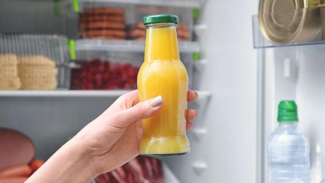 Unhealthy orange juice bottle held in front of fridge
