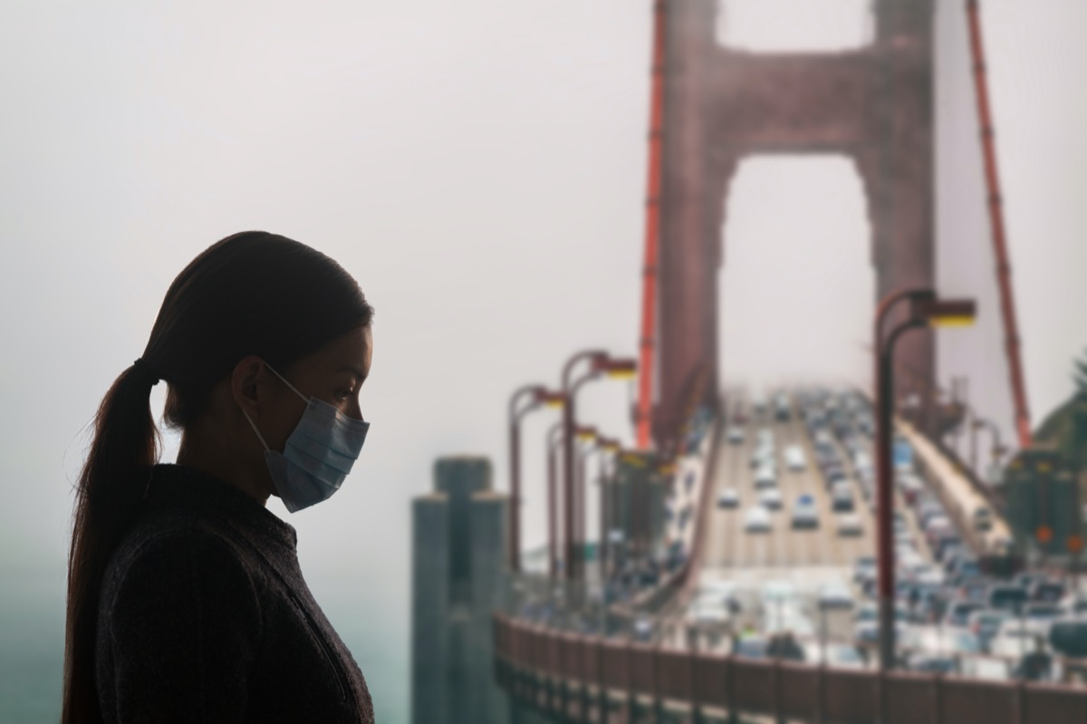 Woman with surgical mask for corona virus covid-19 protection in San Francisco, USA, in front of Golden Gate Bridge. California