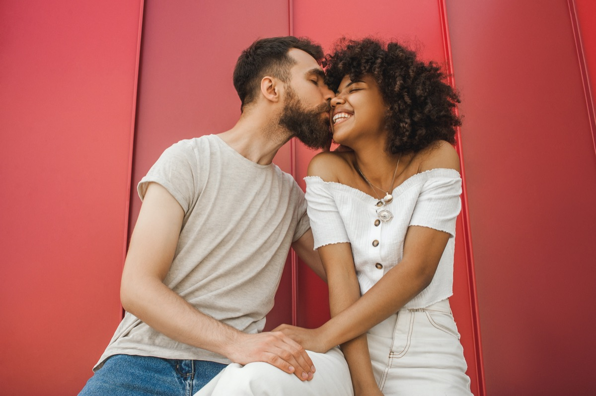 handsome young man kissing happy girlfriend
