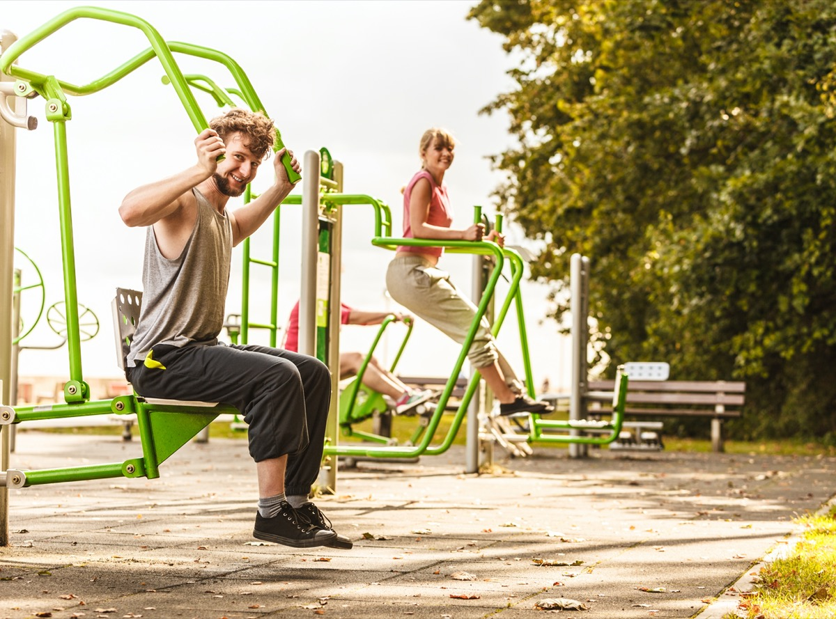 Muscular strong guy and girl in training suit working out at outdoor gym.